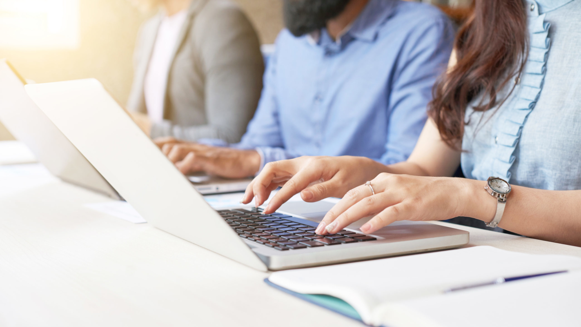 Close-up of business people sitting in a row and typing on laptop while sitting at office desk